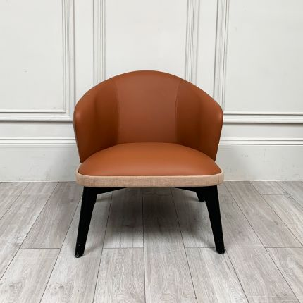 A luxurious leather and linen armchair with matte black legs and a linen outer back and rim
