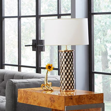 A stylish, porcelain table lamp with a chic geometric pattern and brass accents