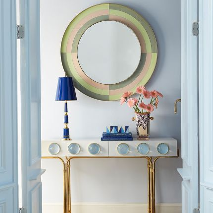 A stylish round mirror with multicoloured reverse painted glass