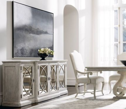 Elegant, distressed sideboard with decorated panel doors.