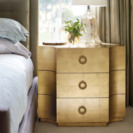 A golden bedside table with three drawers.