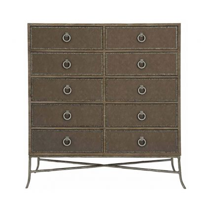A rustic and moody tallboy with ten drawers, tarnished metal details and upholstered drawer panels in a dark performance fabric
