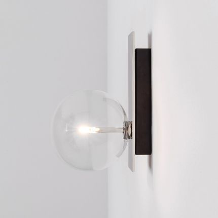 An elegant black gunmetal wall lamp with a transparent glass lampshade