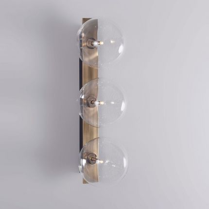A glamorous industrial-style triple light wall lamp in a lacquered burnished brass finish