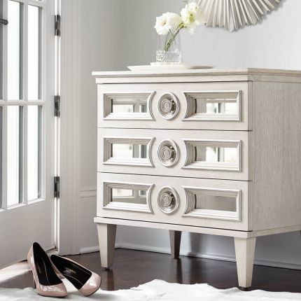 An alluring white oak veneer bedside table by Bernhardt with antique mirrored glass panels, Silver Luster highlights and a Manor White finish