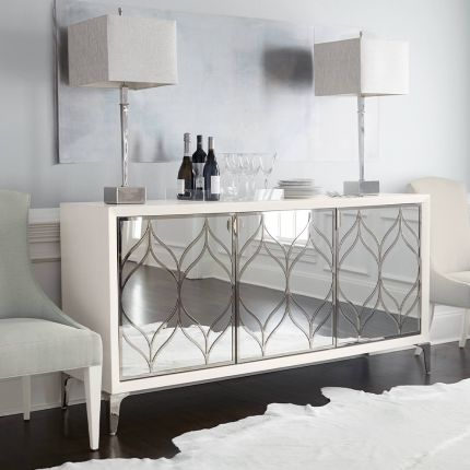 A dazzling buffet with three mirrored glass doors featuring decorative stainless steel overlays and an abundance of internal storage