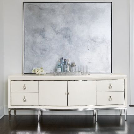 A contemporary entertainment unit with polished stainless steel accents, four drawers, two doors and internal shelving