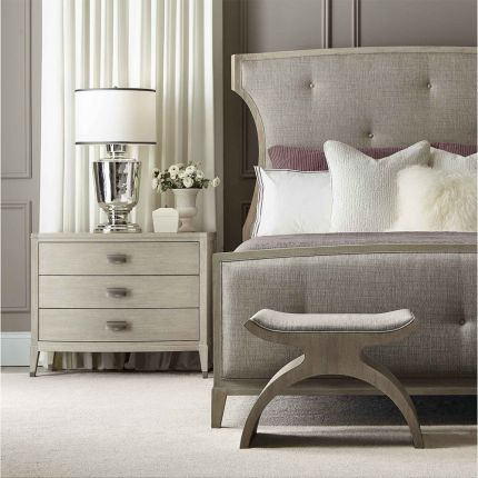 A chic minimal natural wood bedside table with tarnished nickel accents