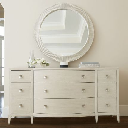 A contemporary round mirror by Bernhardt with a coastal style wooden frame