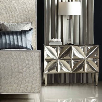 A radiant bedside table by Bernhardt featuring two carved floral patterned push to open doors and a white interior finish