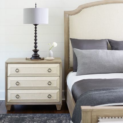 A stylish natural wood bedside table with performance fabric and tarnished nickel handles