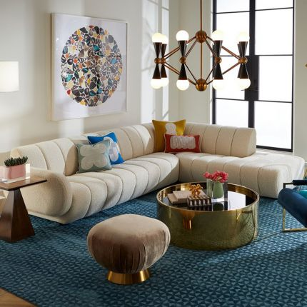 A sumptuous sectional sofa by Jonathan Adler upholstered in an Olympus Ivory bouclé with stylish deep channelled cushions and capsule-shaped arms