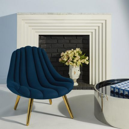 A glamorous channel-tufted armchair with polished brass legs