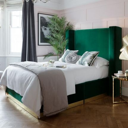 Glamorous, art deco bed with fluted wing headboard, sat on a brass plinth