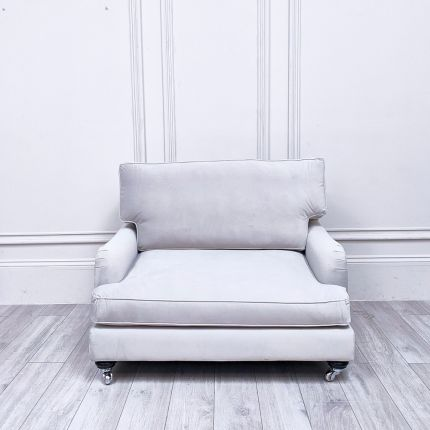 A contemporary, velvet loveseat modern black and chrome castors and a sumptuous back cushion.