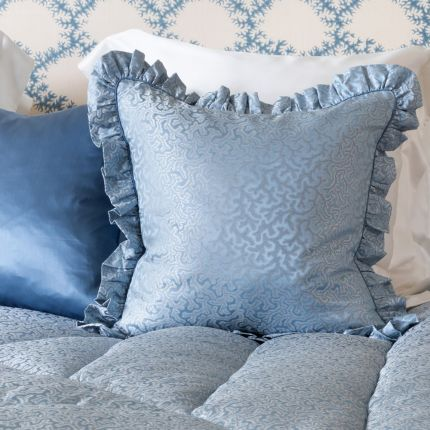 An elegant blue silk cushion with a coral jacquard pattern and frills