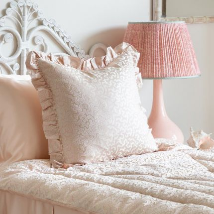 A luxurious pink silk cushion with a coral jacquard pattern and frills