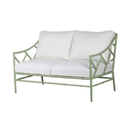 A stylish sage green outdoor two seater sofa with white cushions