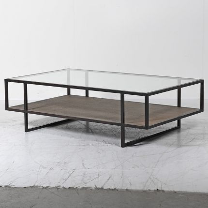 A luxurious two-tier coffee table with a  glass surface and wicker/mdf lower shelf