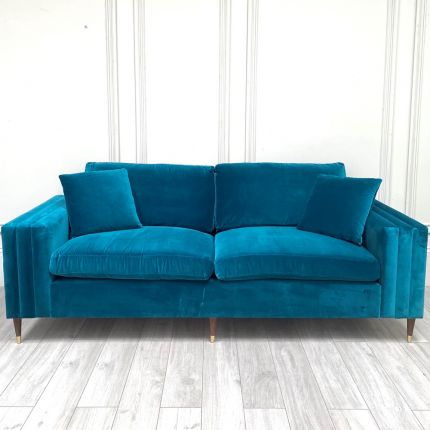 A luxurious teal coloured 4-seater sofa with scatter cushions