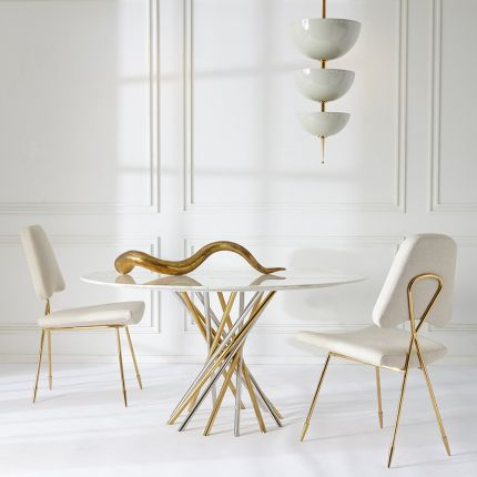 A contemporary marble table with a nickel and brass base