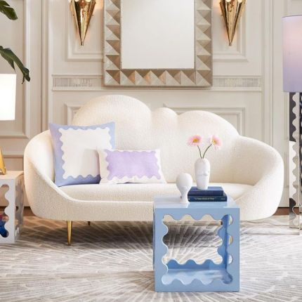 A luxurious cloud-shaped sofa with boucle upholstery and polished brass legs