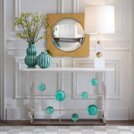A stylish polished nickel console with emerald acrylic cabochons and marble top