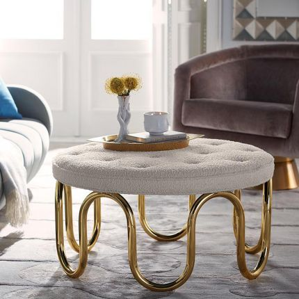 Luxurious circular ottoman upholstered in ivory boucle fabric with polished brass pipe base