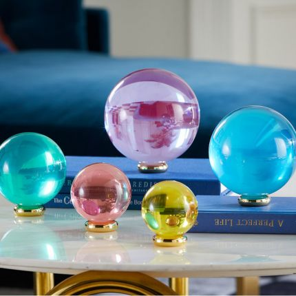 A set of luxurious coloured acrylic orbs with polished brass stands