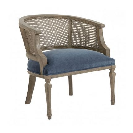 A luxurious blue velvet French-style armchair with caned detailing