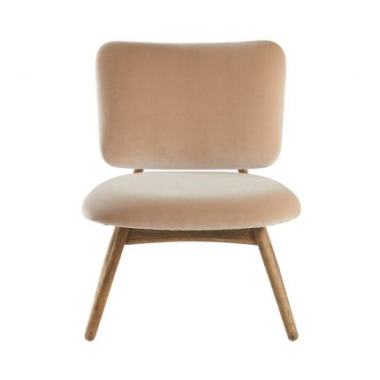 A luxurious nude beige velvet armchair with a natural oak wood frame