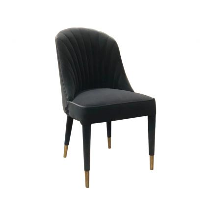 A stunning velvet upholstered dining chair with a fluted back and brushed brass-effect accents