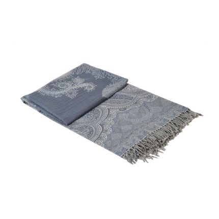 A luxurious blue and grey throw with elaborate, woven detailing and tassels