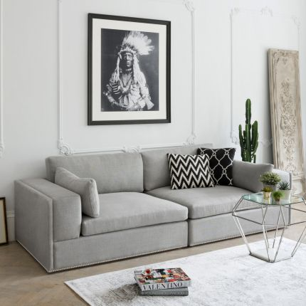Luxury sofa with deep seat cushions, wide low arms, and nickel studded base