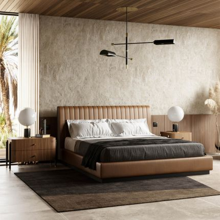 A luxurious leather bed with a fluted headboard and a wrought iron plinth