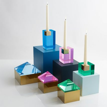 A glamorous candleholder by Jonathan Adler featuring a blue acrylic block fitted with a solid brass candleholder
