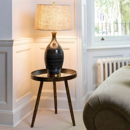 A luxurious, textured ceramic side lamp with a brushed brass base and a linen shade