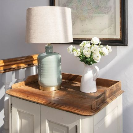 An elegant duck egg table lamp with a linen shade and brushed brass base