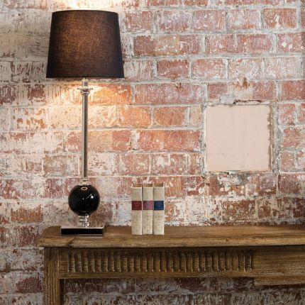 An elegant slender table lamp with black and nickel detailing and a black linen shade