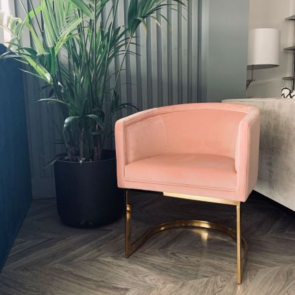 A stylish dining chair with a polished brass frame