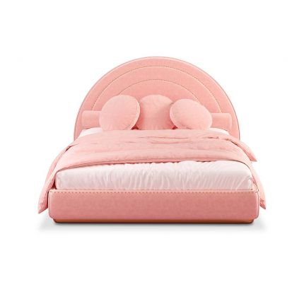 A delicate and chic pink pastel velvet bed with a curved headboard