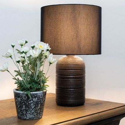 An artistic and distinctively designed polyresin table lamp with a cotton lampshade