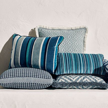 A blue velvet outdoor cushion with various stripes with complementary dark blue piping.