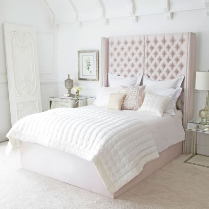 Luxury hotel-style bed with tall deep buttoned headboard and stud detailing