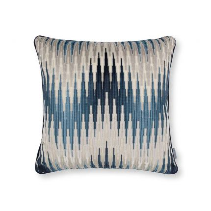 A cushion with a velvet chevron pattern in blue and cream hues.