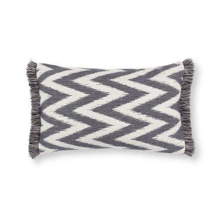A grey, zig zag patterned outdoor cushion with fringe details.