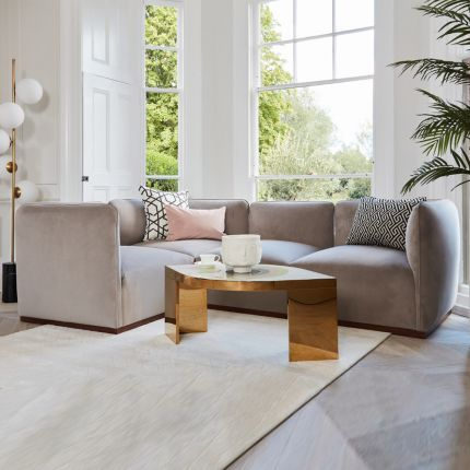 A chic grey velvet corner sofa with a brown base