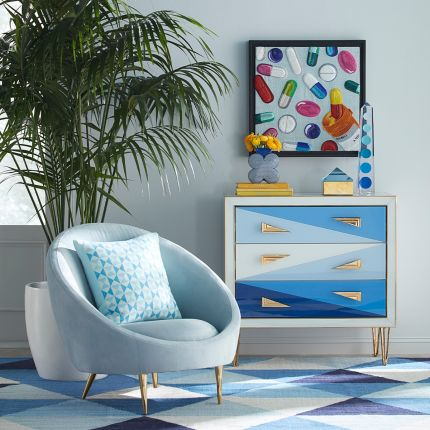 A stylish, modern armchair with light blue velvet upholstery and polished brass legs