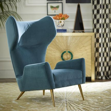 A stylish grey wing back armchair with grey velvet and wooden legs