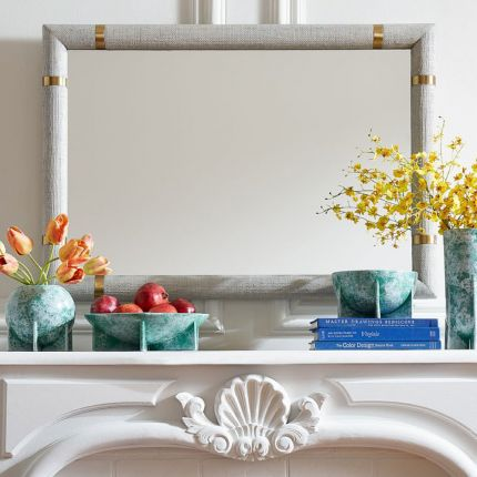 An exotic, stained raffia mirror with polished brass accents